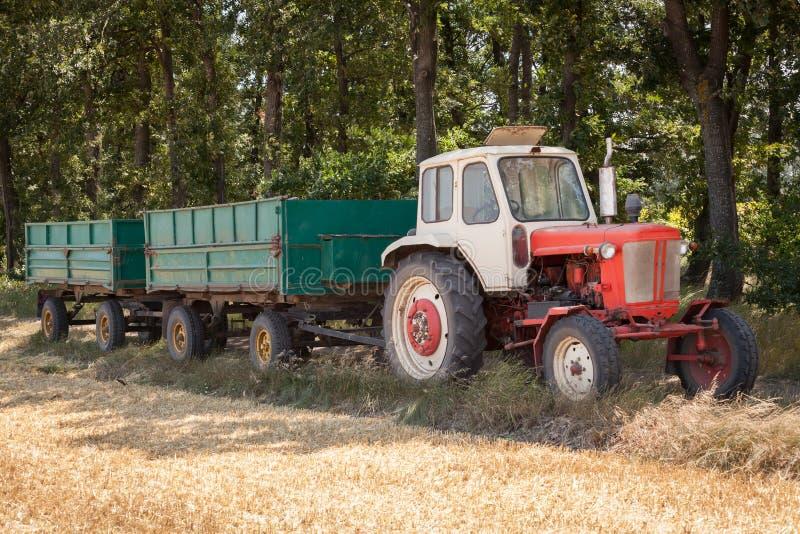 Vecchio trattore con i rimorchi sul campo fotografie stock