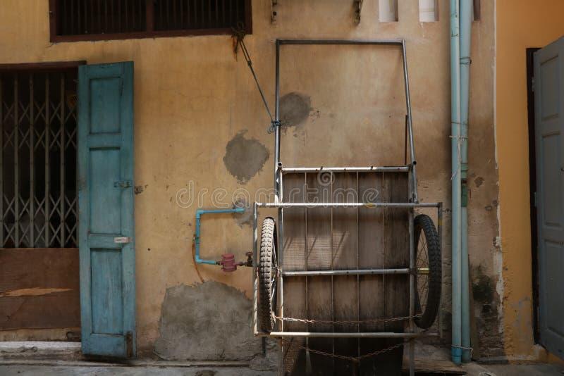 Vecchio triciclo sulla parete d'annata fotografie stock