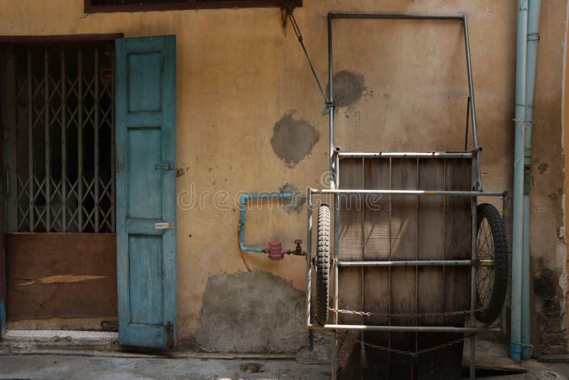 Vecchio triciclo sulla parete d'annata immagini stock libere da diritti