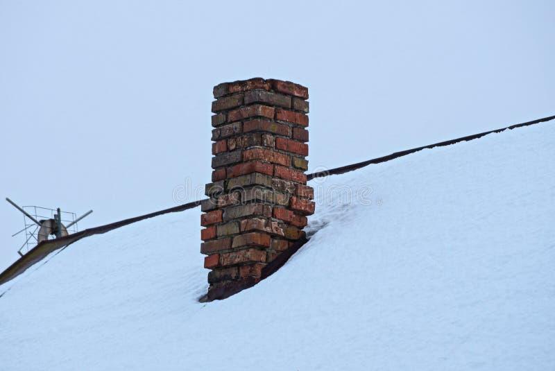 Vecchio tubo marrone del camino del mattone sul tetto in neve bianca immagini stock