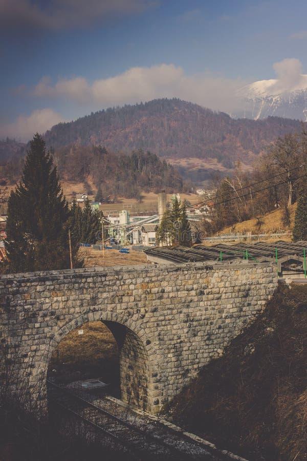 Vecchio tunnel del mattone sopra il lago sanguinato vicino ferroviario della singola pista immagini stock