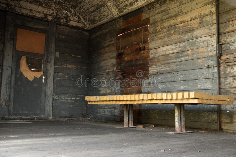 Vecchio vagone di legno misero dall'interno, con il banco immagini stock