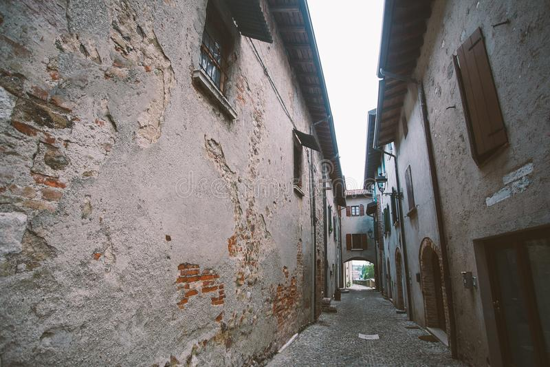 Vecchio vicolo stretto in villaggio toscano - vicolo italiano antico in Montalcino, Toscana, Italia fotografia stock libera da diritti