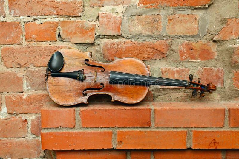 Vecchio violino e muro di mattoni vuoto immagine stock