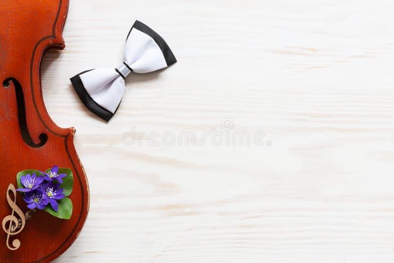 Vecchio violino, piccolo mazzo di fiori viola di hepatica e cravatta a farfalla sui precedenti di legno bianchi Vista superiore,  immagine stock libera da diritti
