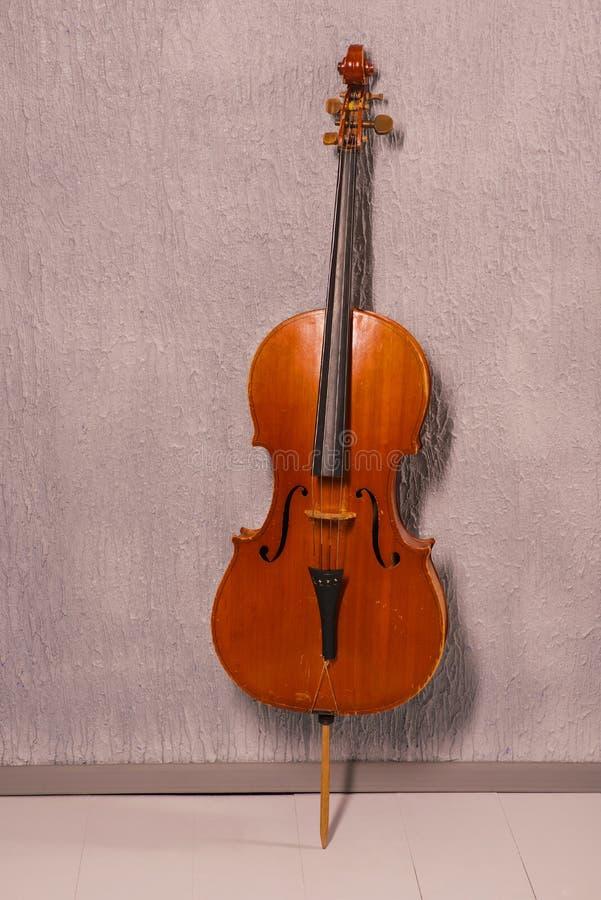 Vecchio violoncello avariato che sta vicino ad una parete strutturata grigia fotografia stock