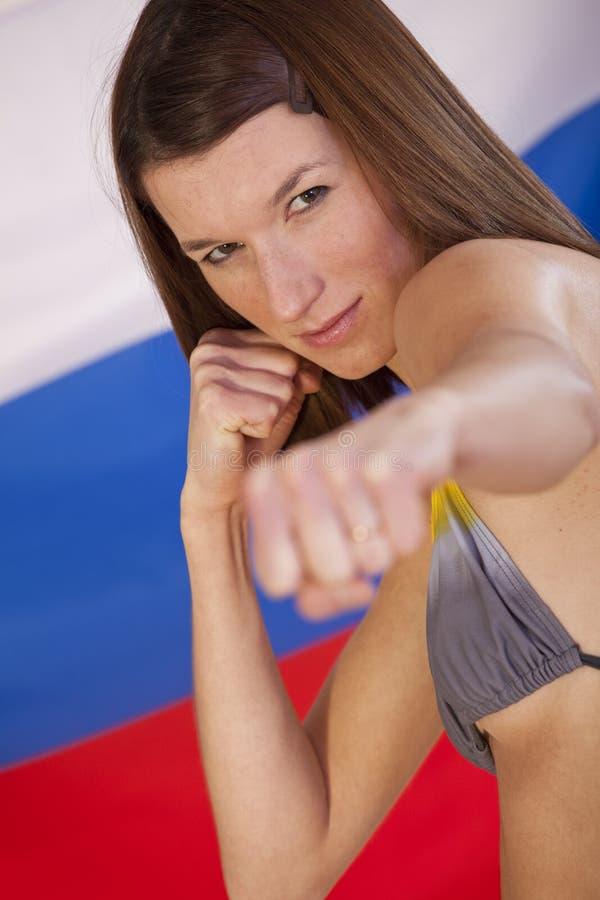 Vechtende vrouw over Russische vlag stock afbeelding