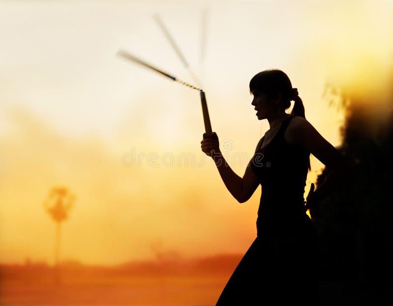 Vechtsporten, vrouwen en nunchaku in handensilhouet in zonsondergang stock afbeelding