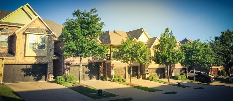 Vecindad de la novedad con la fila de casas atadas y de puertas dobles del garaje fotos de archivo libres de regalías