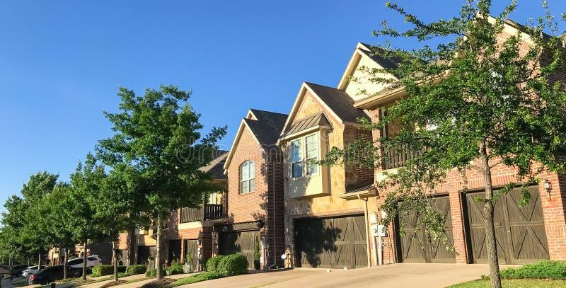 Vecindad de la novedad con la fila de casas atadas y de puertas dobles del garaje fotografía de archivo libre de regalías