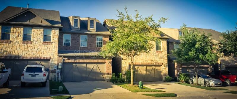 Vecindad de la novedad con la fila de casas atadas y de puertas dobles del garaje fotos de archivo