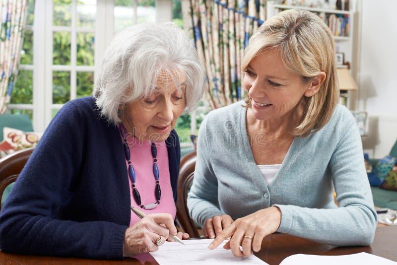 Vecino femenino que ayuda a la mujer mayor a llenar el formulario fotografía de archivo libre de regalías