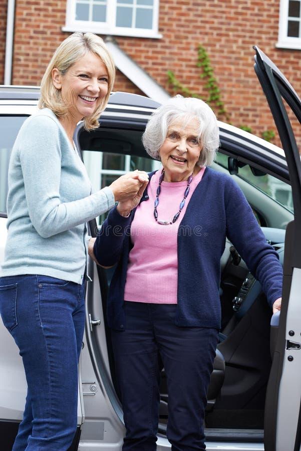 Vecino femenino que da a mujer mayor una elevación en coche fotografía de archivo libre de regalías