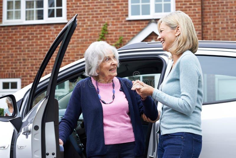 Vecino femenino que da a mujer mayor una elevación en coche imagen de archivo