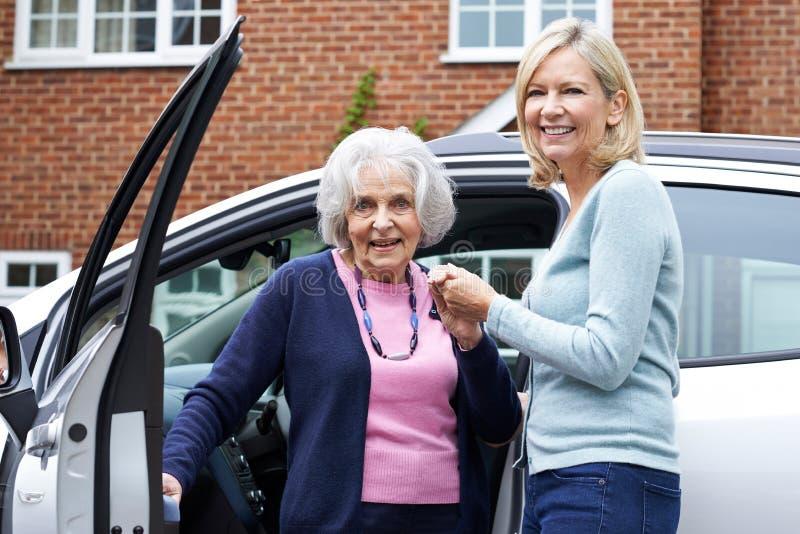 Vecino femenino que da a mujer mayor una elevación en coche fotos de archivo