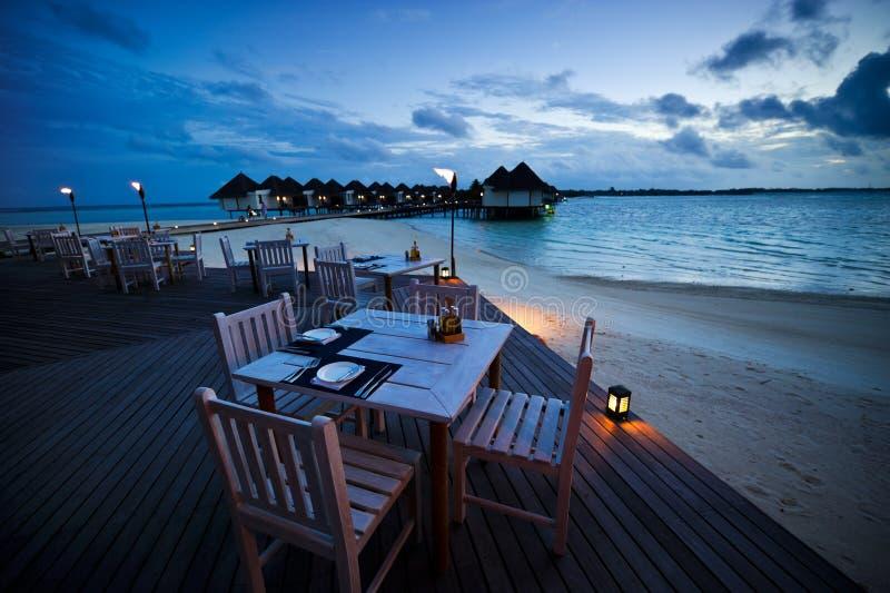Vector de cena en el restaurante al aire libre de la playa fotos de archivo