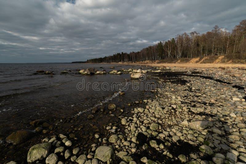 Veczemju Klintis -巨石城海滩在波儿地克的国家拉脱维亚在2019年4月-与愚钝的云彩和一点太阳的多云天 图库摄影