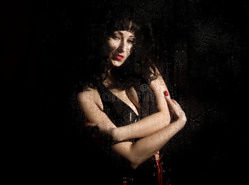 Vedova nera in un velo, pizzo d'uso della donna triste misteriosa posando dietro il vetro trasparente coperto dalle gocce di acqu immagini stock libere da diritti
