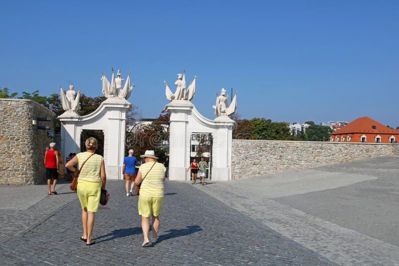 Veduta dalle spalle di due donne non identificate vestite di identico vestito vicino al cancello del castello di Bratislava a Bra fotografia stock libera da diritti