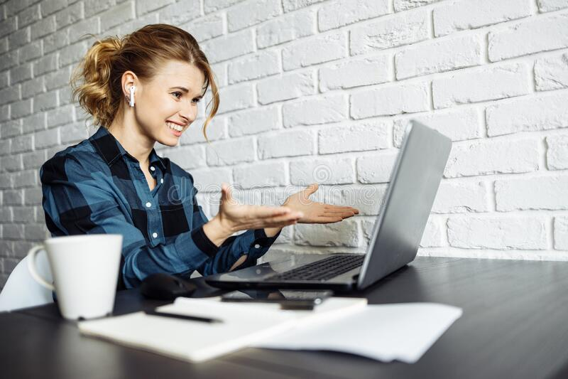 Veduta laterale della donna felice freelancer seduta a tavola con il computer portatile immagini stock