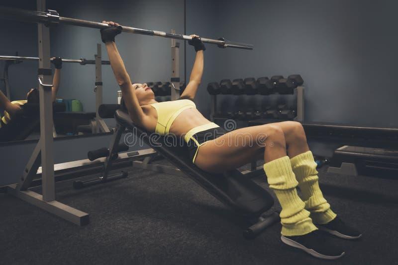 Veduta laterale per donna sportiva e adatta che si esercita con barbell sullo sfondo della palestra Una sorridente sdraiata sulla fotografia stock