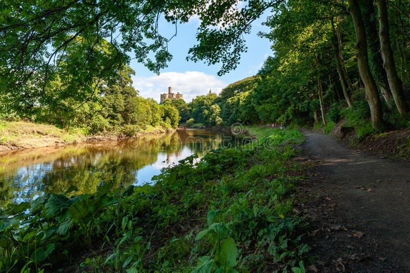 Veduta lungo il fiume Coquet e strada per il castello di Warkworth in una giornata di sole fotografia stock