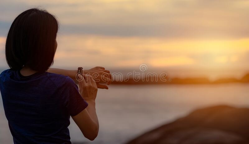 Veduta posteriore Una donna asiatica tocca una banda intelligente dopo essersi presentata al mattino con il cielo del tramonto su fotografia stock