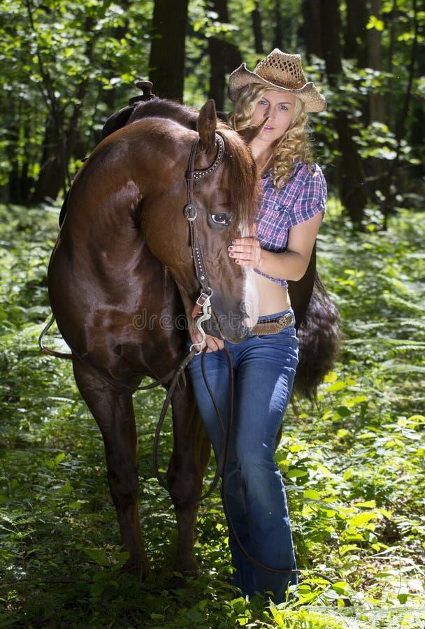Veedrijfster met paard in bos stock fotografie