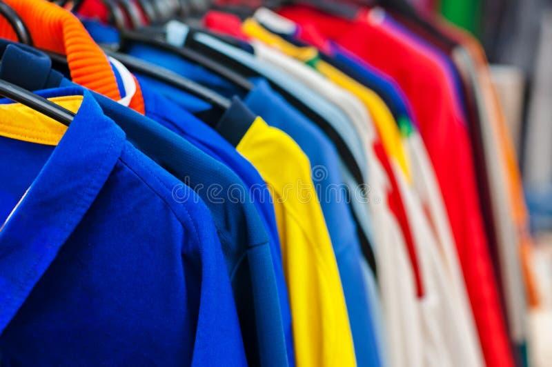 Veel heldere kleurrijke kleren op hangers in winkel royalty-vrije stock foto's