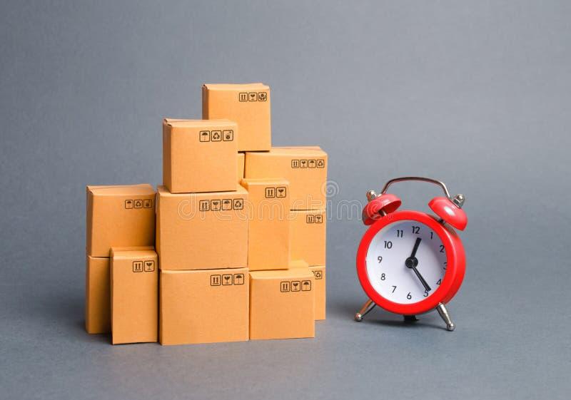 Veel kartonnen dozen en een rode wekker Expresleveringsconcept Optimalisering van logistiek en levering, verbetering royalty-vrije stock afbeelding