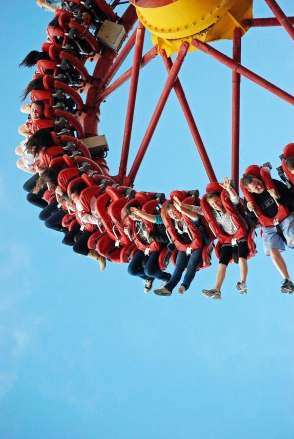 Veel tienersjongeren die pret op wilde rit hebben bij themapark stock fotografie