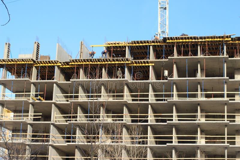 Veel torenbouwwerf met kranen en de bouw met blauwe hemelachtergrond stock afbeelding
