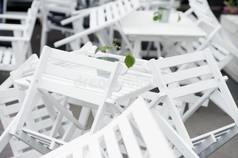 Veel van omgekeerde witte plastic stoelen op lijsten in gesloten restaurant op terrasclose-up Mooie grafische chaos stock afbeeldingen