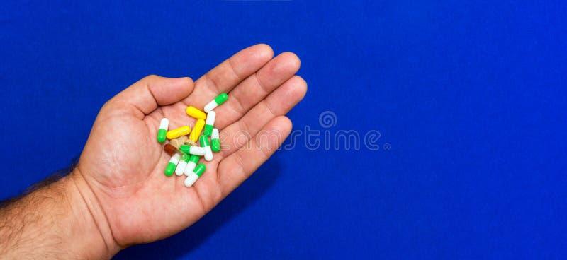 Veel verschillende pillen in een mannelijke hand close-up. Blauwe blauwe achtergrond. Het begrip farmaceutisch bedrijf. Gezondheid stock fotografie