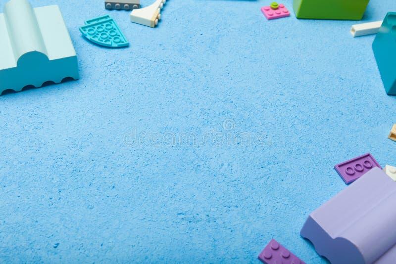 Veelkleurige plastic bouwstenen van een aannemer op een blauwe achtergrond Lege ruimte voor tekst De idylle van de zomer royalty-vrije stock foto