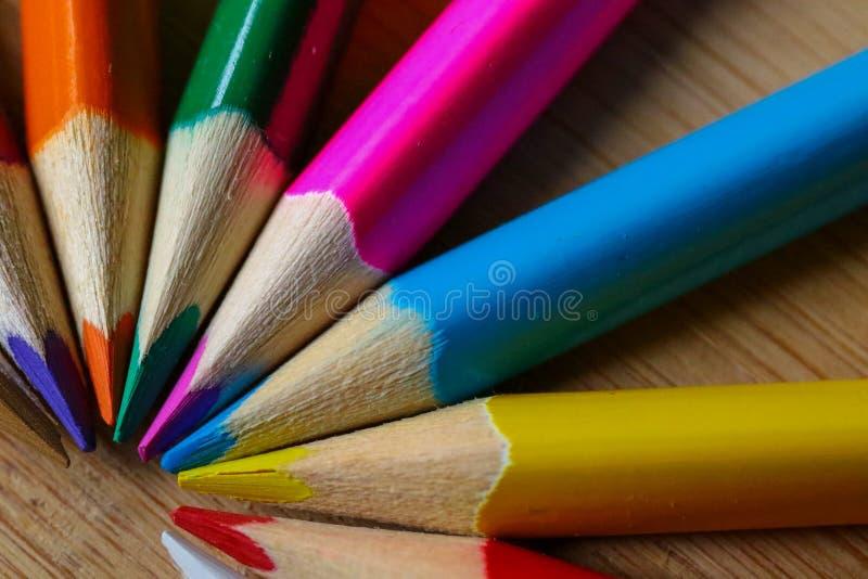 Veelkleurige potloden die een kleuren halve die cirkel vormen op houten achtergrond wordt geïsoleerd stock afbeelding