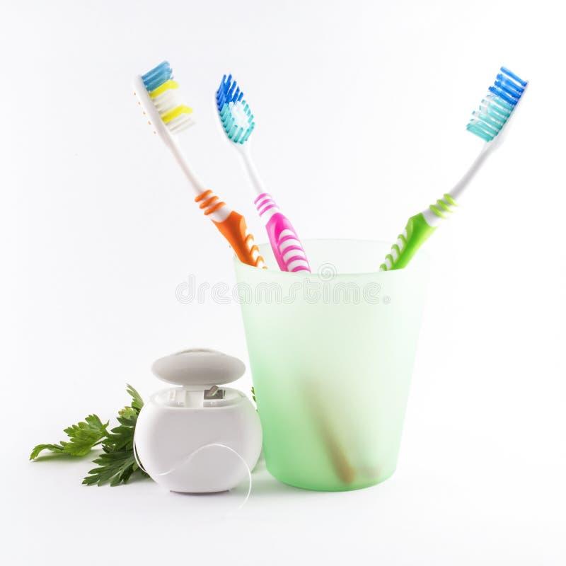 Veelkleurige tandenborstels en tandzijde op witte achtergrond stock afbeelding