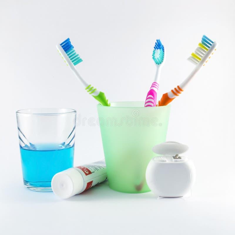 Veelkleurige tandenborstels, tandzijde, tandpasta en mondspoeling op witte achtergrond stock afbeelding