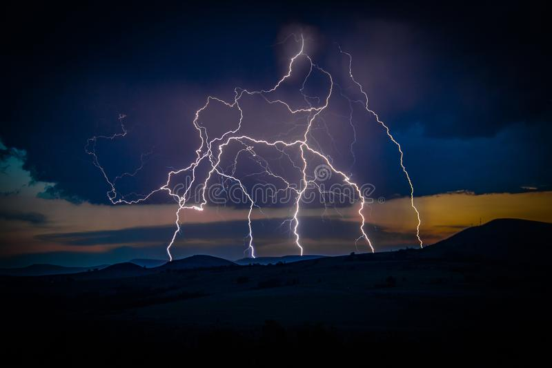 Veelvoudige bliksemstakingen op verre berg stock afbeeldingen