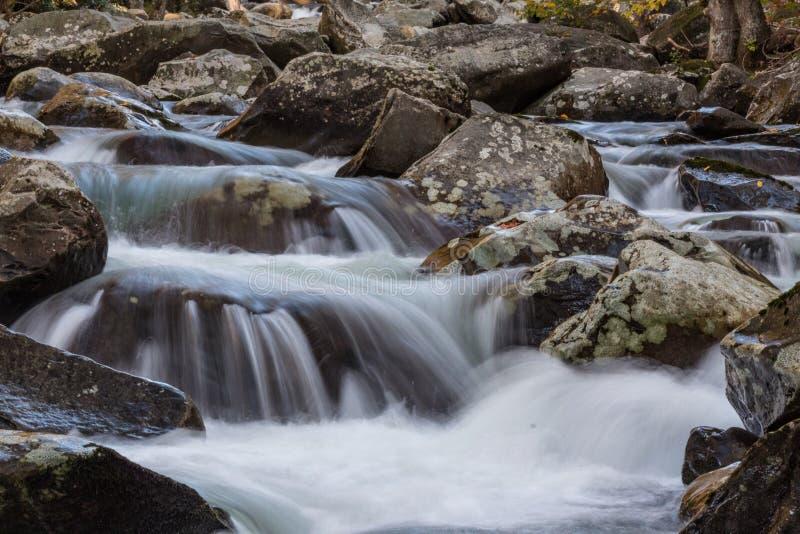 Veelvoudige cascades van water over korstmos behandelde rotsen in Great Smoky Mountains stock fotografie