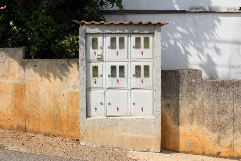 Veelvoudige elektrometerdozen en veiligheidsschakelaars binnen zichtbaar door kleine vensters opgezet op concrete muur naast bede stock afbeelding