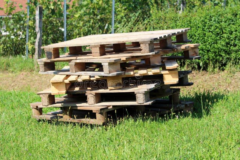 Veelvoudige houten pallets voor later gebruik verlaten op kleine stapel in binnenplaats stock foto