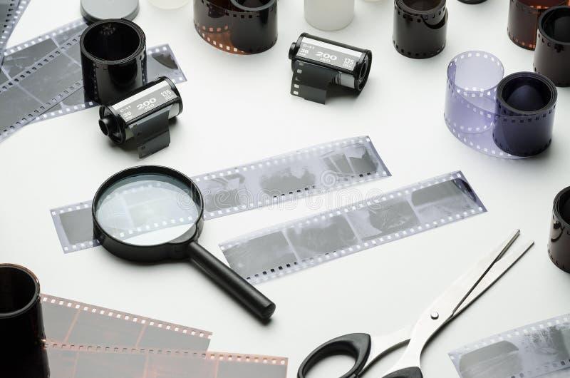 Veelvoudige 35mm films, vergrootglas en schaar op witte achtergrond stock afbeeldingen