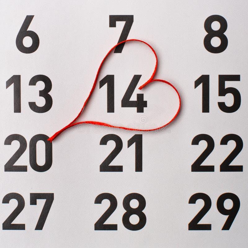 veertiende van Februari-kalenderherinnering met een rood satijnhart royalty-vrije stock foto's