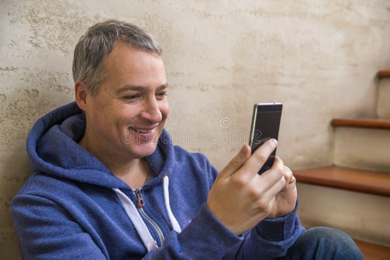 Veertig van de oude zakenmanjaar plaatsing op treden binnen de bureaubouw die op een mobiele telefoon kijken royalty-vrije stock foto