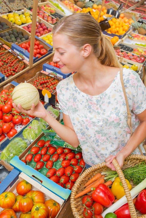 Veg del canestro della tenuta di signora in un melone della mano in altro fotografie stock libere da diritti