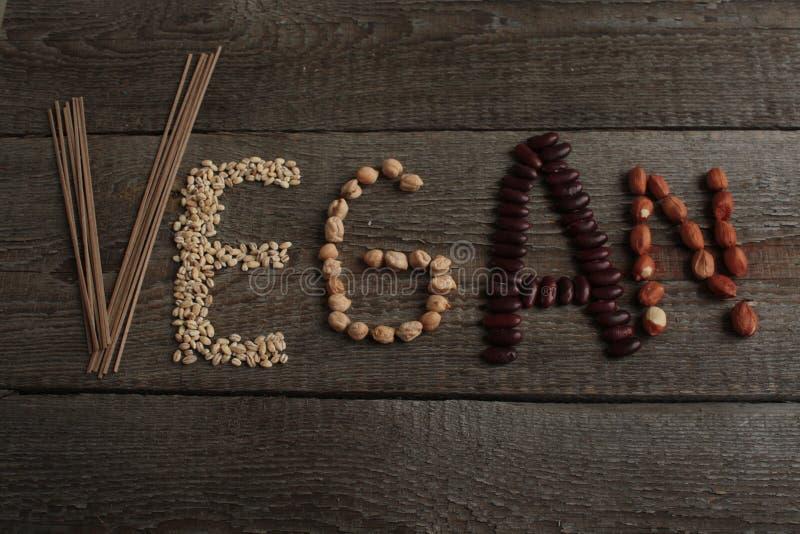 Vegan слова написанный еду завода: фасоли, гайки идет vegan стоковое фото rf