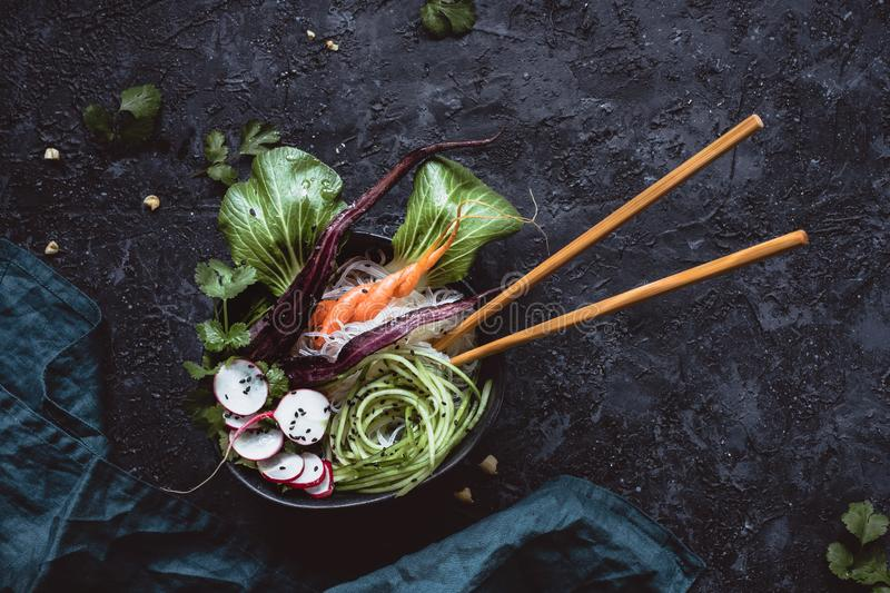 Vegan bowl with chopsticks. Asian salad with rice noodles, carrot, radish and cucumber on black background. Top view stock photography