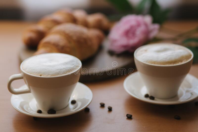 Vegan breakfast at home. Cappuccino with coconut milk and two empty vegan croissants. Morning with coffe. Pink peony. Flower on table stock photography