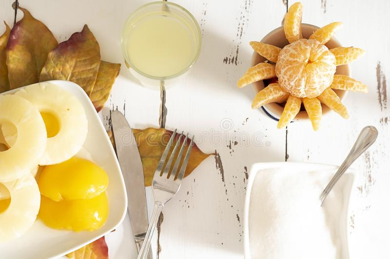 Vegan breakfast. With pineapple and peach slices and natural pineapple juice and tangerine royalty free stock photo